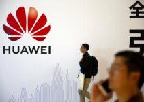 Pria Berlalu Lalang di depan Papan Iklan Huawei di Beijing, Tiongkok (China) Lisensi Usaha di AS